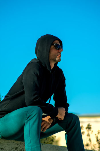 Man wearing sunglasses sitting against clear blue sky