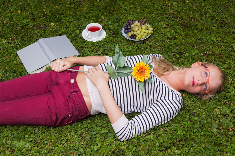 High angle view of young woman holding flower while lying on grassy field