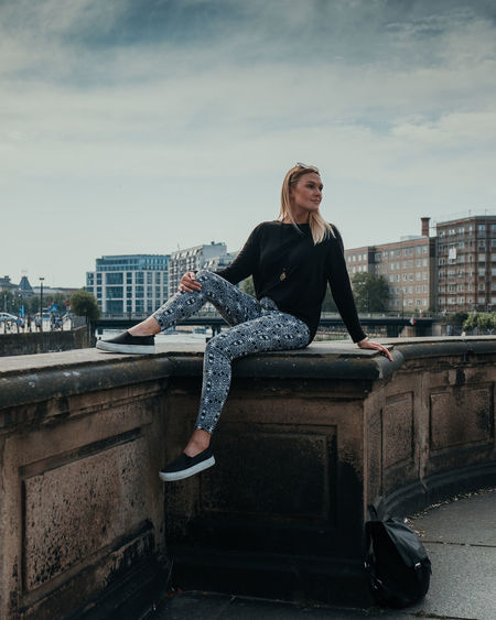 Full length of woman sitting in city against sky