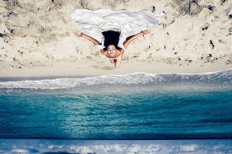 High angle view of woman sunbathing at sandy beach