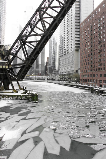 Bridge over river amidst buildings in city during winter