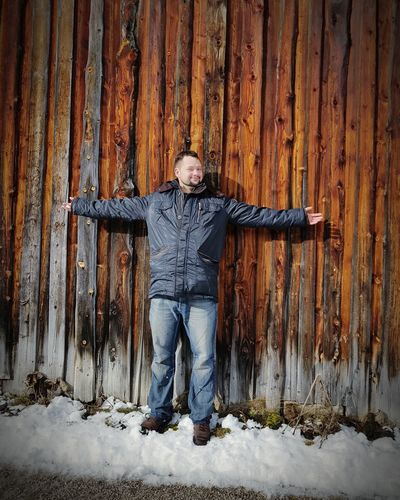 Portrait Of Smiling Man Standing By Wooden Fence