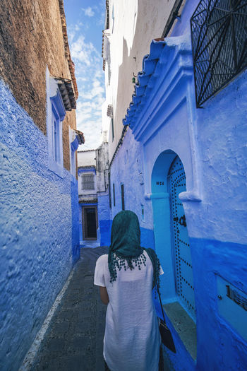 """""""The Blue City"""" We travelled from Sevilla to Tarifa, then took a ferry to Tangier, then a taxi to Chefchaouen, Morocco. EyeEmNewHere a new beginning Chefchaouen Morocco Beauty Blue City Blue Medina Digital Nomad Rear View Architecture Built Structure Building Exterior One Person Real People Lifestyles Day Building Leisure Activity Women Adult Standing City Residential District Three Quarter Length Clothing Outdoors Alley"""