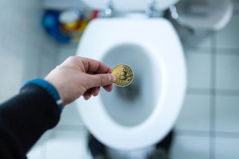 High angle view of person holding bit coin over toilet bowl