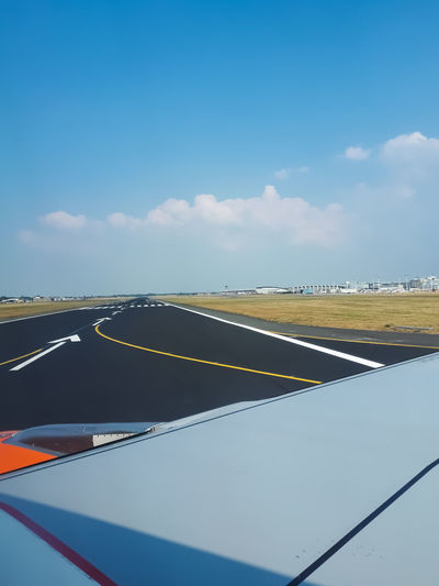 Airplane on road against sky