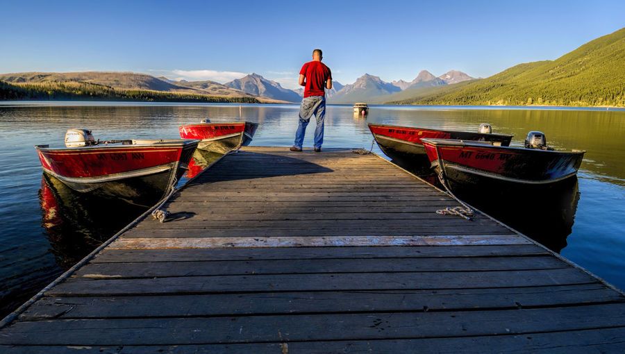 Rear view of man standing on pier amidst boats moored in lake