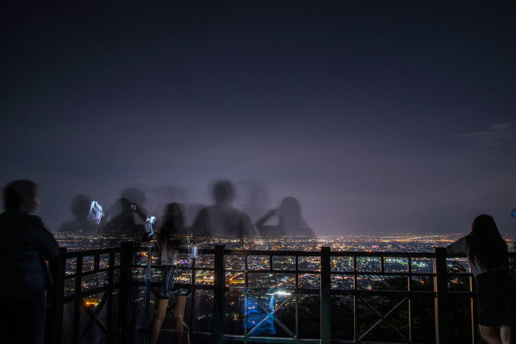 Blurred motion of people on building terrace against sky at night