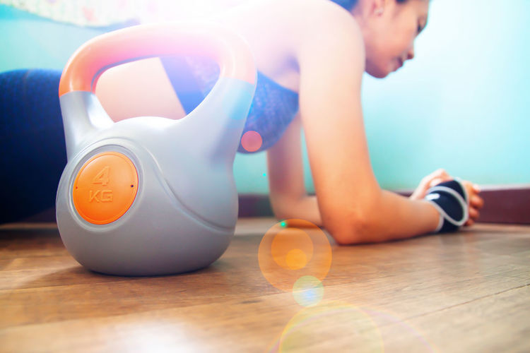 Close-Up Of Kettlebell With Woman Exercising In Background