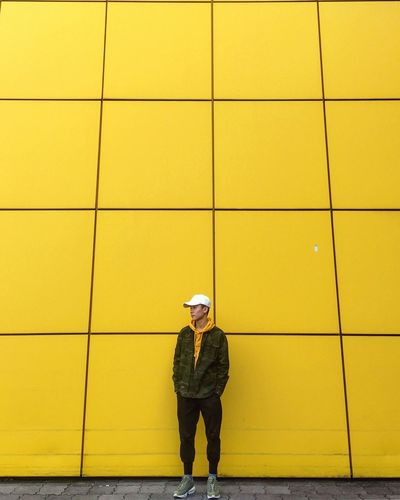 Full length of man standing against yellow wall