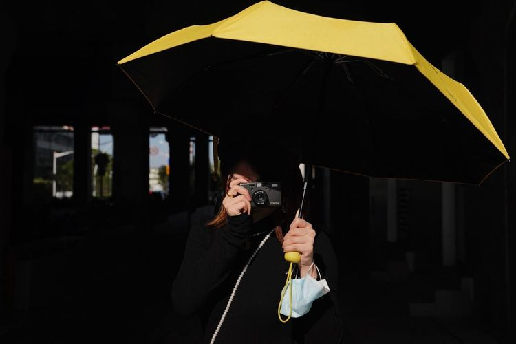 Portrait of woman with umbrella standing in the dark
