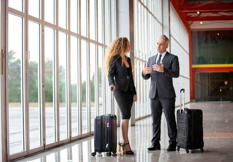 Business couple with luggage talking at airport