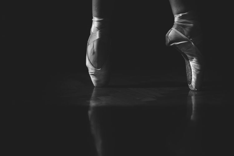 Low Section Of Ballerina Balancing On Toe Against Black Background