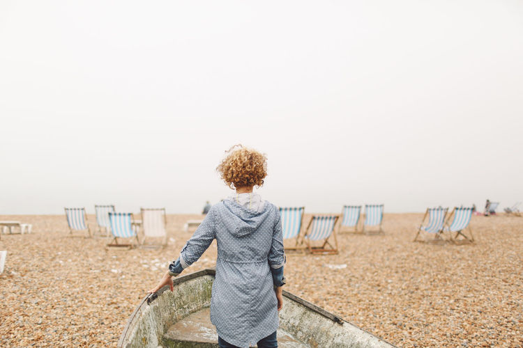 Beach Blonde Brighton Casual Clothing Curly Hair Day Foggy Girl Hat Horizon Over Water Idyllic Leisure Activity Lifestyles Nature Outdoors Rear View Scenics Shore Sky Standing Tranquil Scene Tranquility Vacations People And Places Connected By Travel