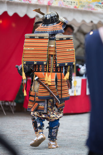 Rear view of man in costume walking on road during event