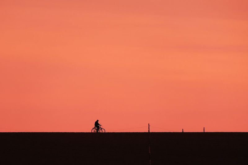Silhouette Man Riding Bicycle Against Orange Sky