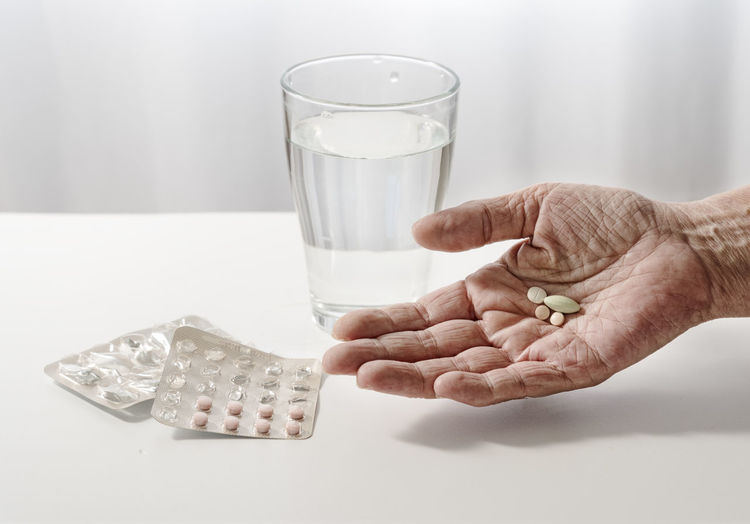 Close-up of wrinkled hand holding medicines on table