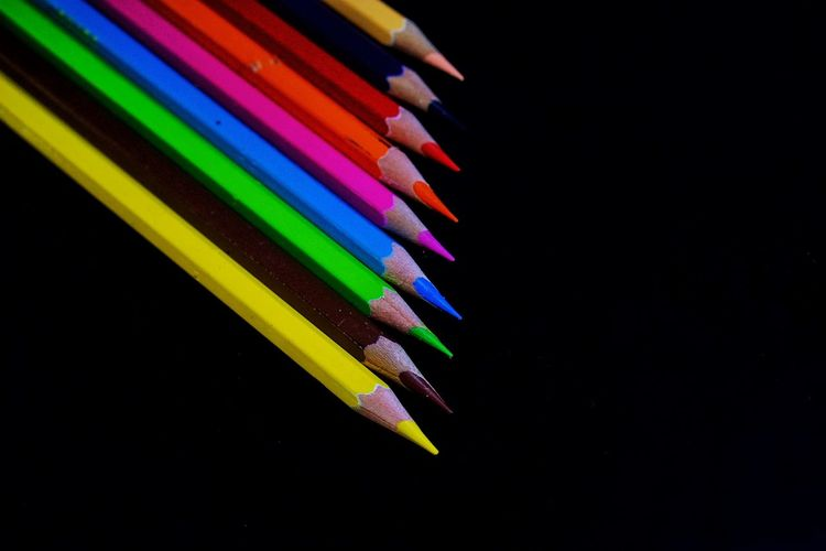High angle view of colored pencils against black background