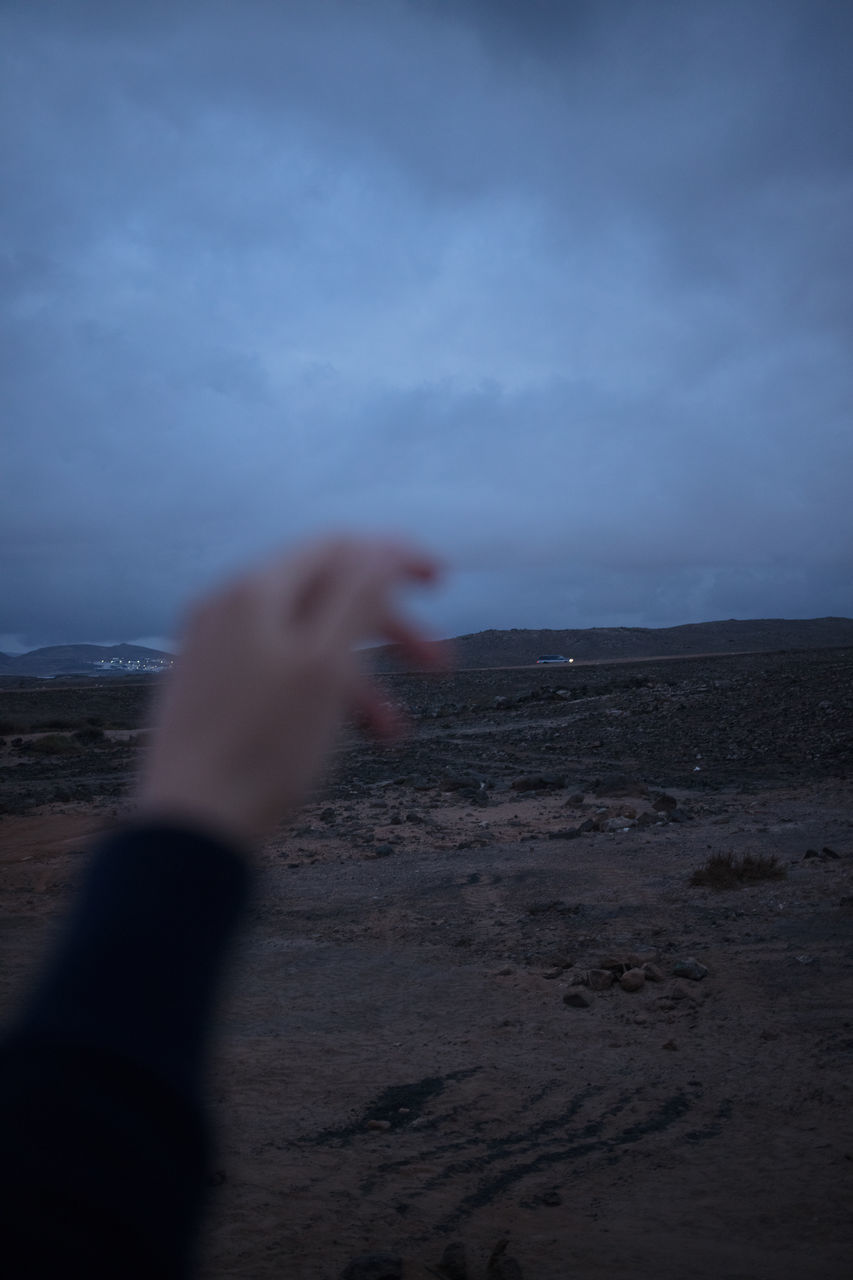 human hand, sky, cloud - sky, hand, human body part, real people, one person, scenics - nature, nature, selective focus, land, focus on background, lifestyles, unrecognizable person, body part, leisure activity, beauty in nature, personal perspective, blurred motion, outdoors, finger, power in nature