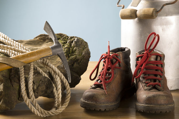 Close-up of piolet and rope on wood by boot on table