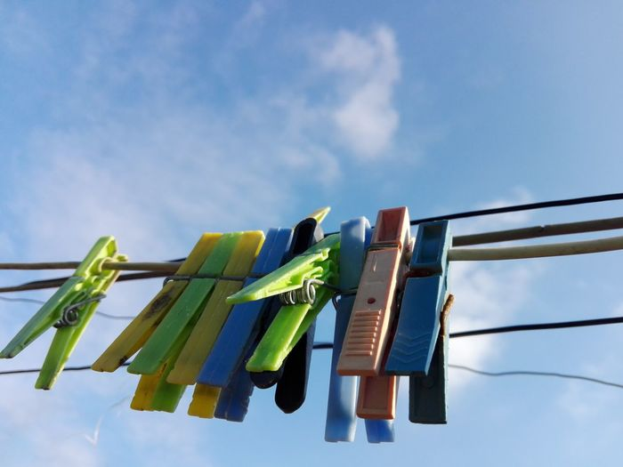 Low Angle View Of Clothespin Hanging On Clothesline Against Sky