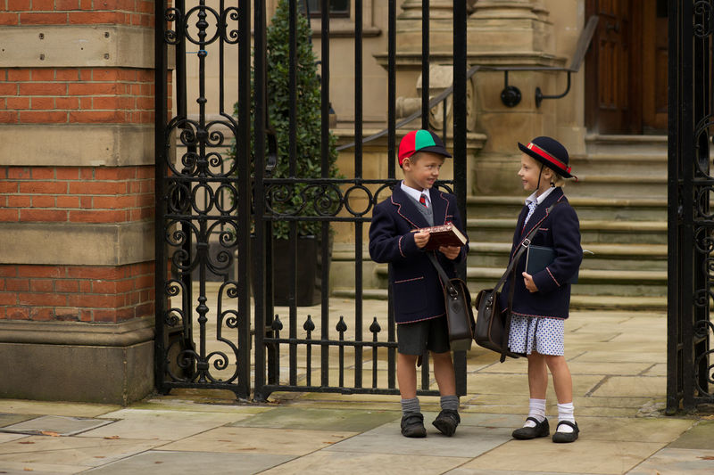 Boy and girl talking while standing by school gate