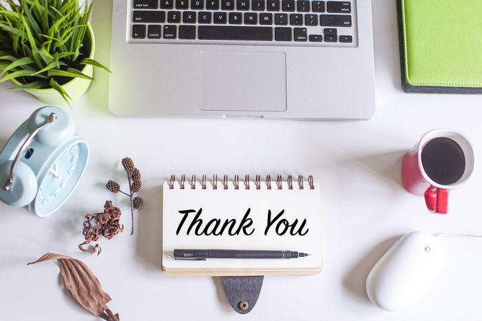 Flat lay view of Office table with laptopl,notebook,dried flowers,pen and a cup of coffee with text THANK YOU. Appreciation Love Terima Kasih Kamu Yang Akan Slalu Bersabar Thanksgiving Appreciate Blessed  Flat Lay Great Thanks  Thanks You