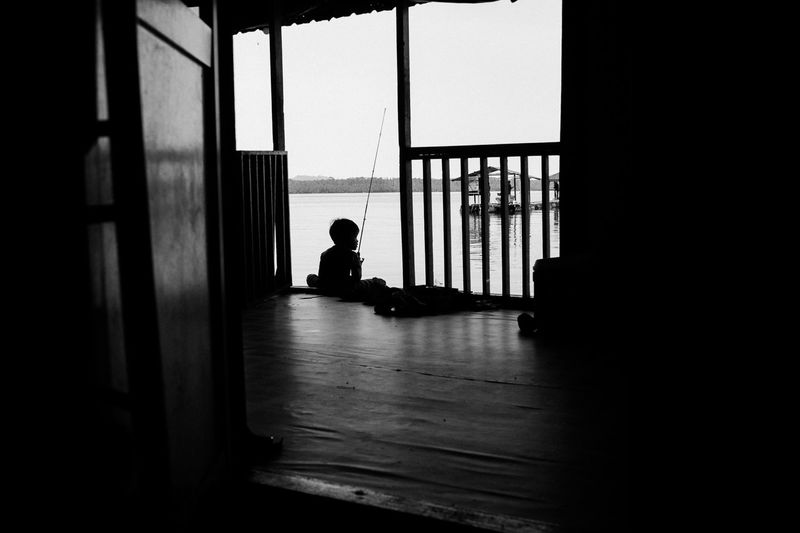 Silhouette man sitting by window in building