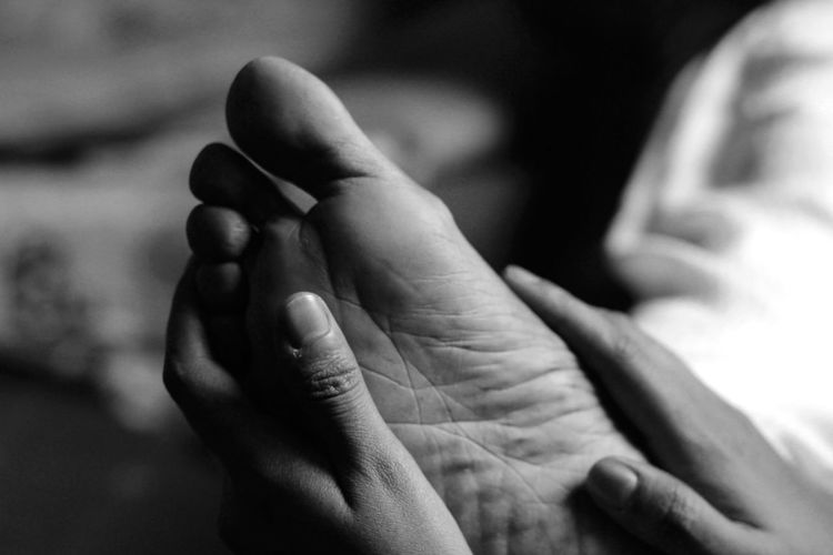 Close-Up Of Hands Touching Feet