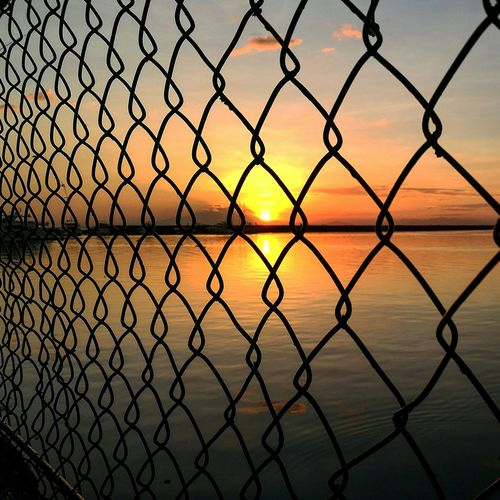 Sunset watching by the bay End Of Day Sun Criscrossed Wires Sky Nostalgic  Hues EyeEm Selects Chainlink Fence Security Metal Sky Protection Sunset Water Beauty In Nature Reflection EyeEmNewHere