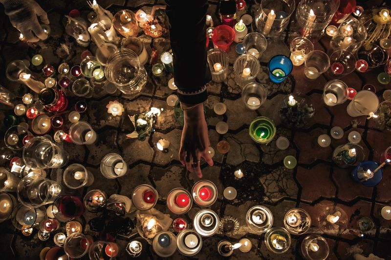 Cropped Hand Arranging Candles On Cobble Street At Night