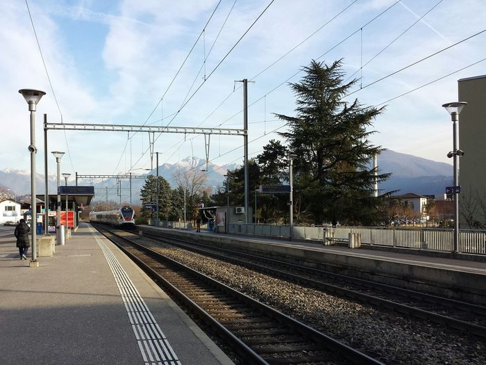 Train arriving at railroad station against sky