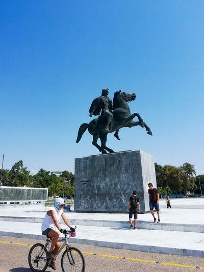 Man riding horse sculpture against clear blue sky