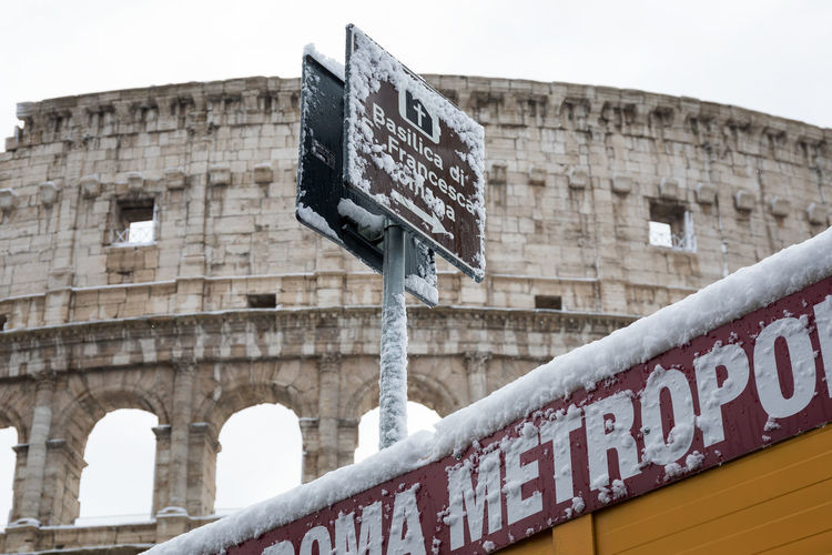 Snow covers the streets of Rome, Italy. The detail of a sign in front of the Colosseum. Architecture Building Exterior Built Structure Capital Letter Close-up Colosseum Communication Day Guidance Information Low Angle View Nameplate No People Outdoors Road Sign Signboard Sky Street Name Sign Text Western Script