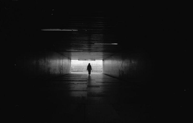 Silhouette person walking in illuminated tunnel