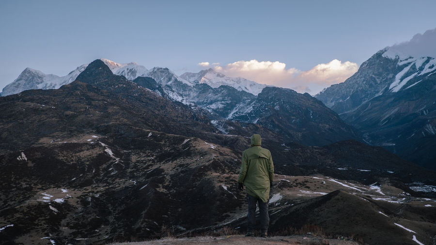 Rear view of woman with snowcapped mountains against sky
