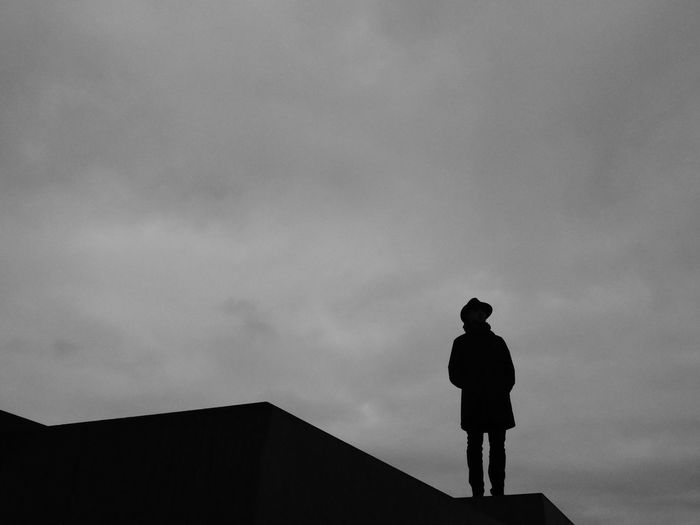 Low angle view of silhouette man standing against sky at dusk