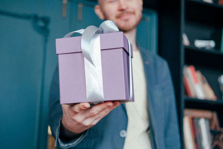 Midsection of man giving gift at home