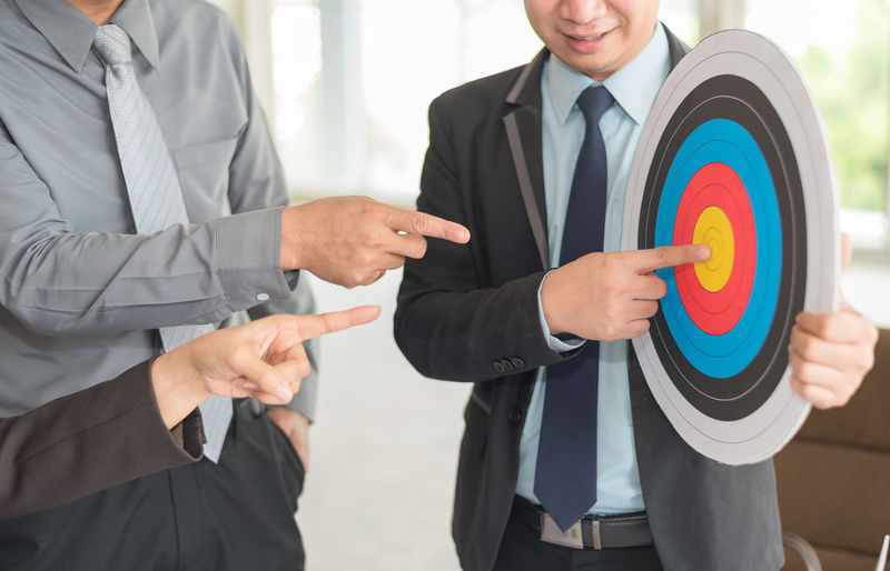 Businessman With Colleagues Holding Dartboard In Office