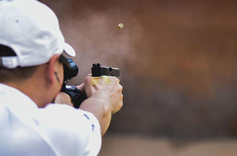 Rear view of man shooting target with handgun