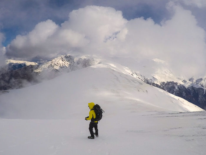Full Length Of Man On Snowcapped Mountain Against Cloudy Sky