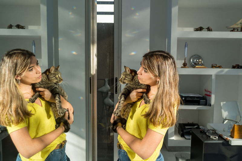 Young woman looking in the mirror with her pet cat in the living room of her home