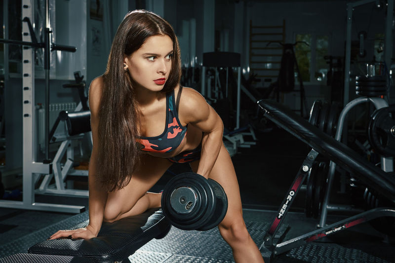 Beautiful Woman Beauty Body Conscious Dumbbell Exercise Equipment Exercising Gym Health Club Healthy Lifestyle Holding Human Body Part Indoors  Lifestyles Muscular Build One Person Real People Sport Sports Clothing Sports Training Strength Strength Training Tank Top Women Young Adult Young Women