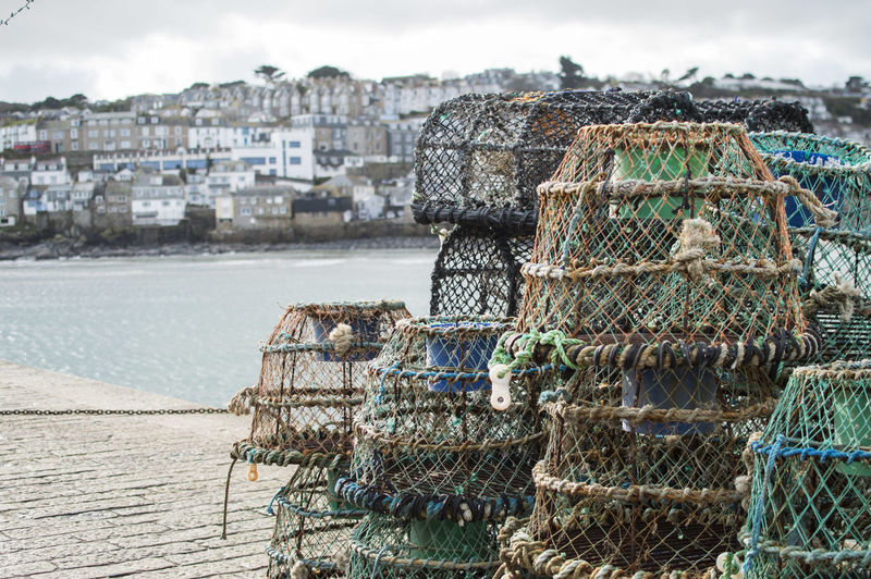 Stack of fishing net on sea against buildings