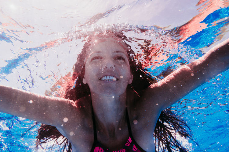 Portrait of a young woman swimming in pool