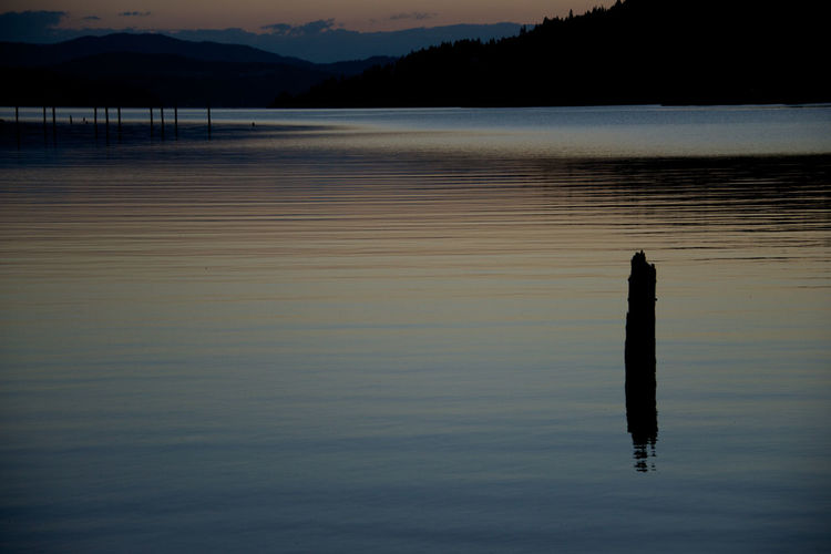 High angle view of wooden post in river against silhouette mountains