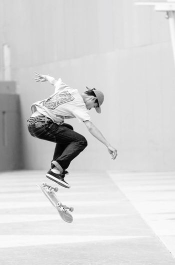 Young Man Performing Stunt With Skateboard At Park