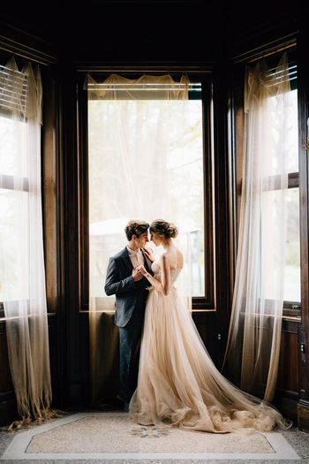 Young couple standing near window