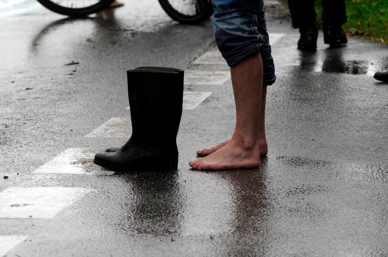 Low section of man standing on wet street
