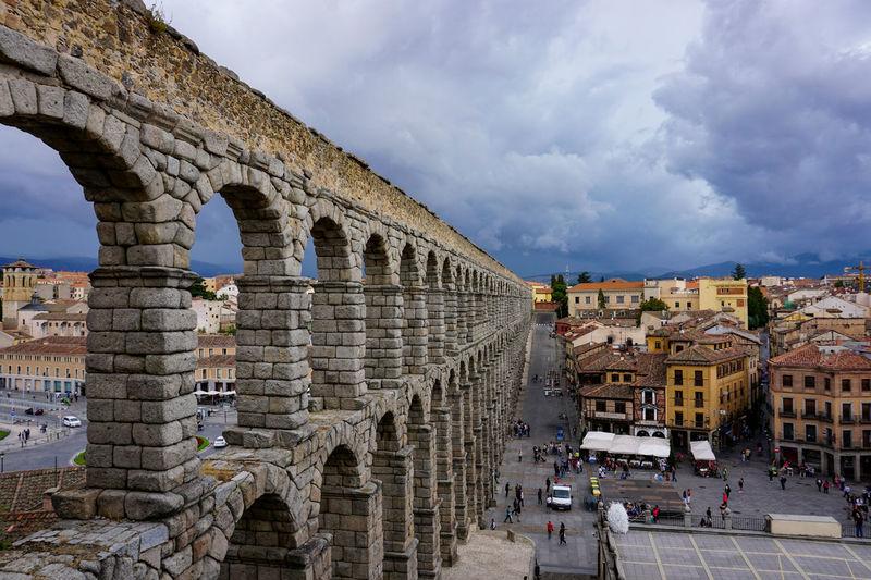 Arch bridge in city against cloudy sky