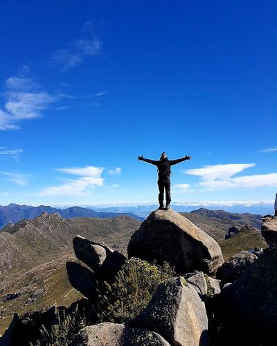 Hiker standing with arms outstretched on boulder at pico das agulhas negras against blue sky
